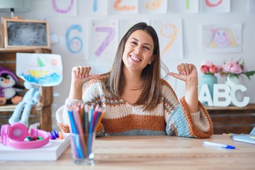 Young beautiful teacher woman wearing sweater and glasses sitting on desk at kindergarten looking confident with smile on face, pointing oneself with fingers proud and happy.
