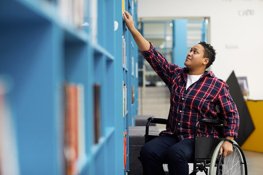 Portrait of disabled student in wheelchair choosing books while studying in college library, copy space