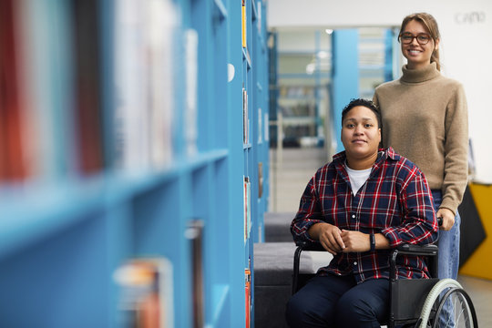 Portrait of two college students, one of them in wheelchair, posing together standing by shelves in library, copy space