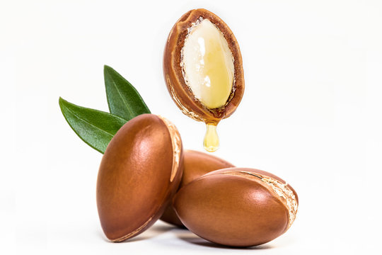 Argan nuts and oil on white background