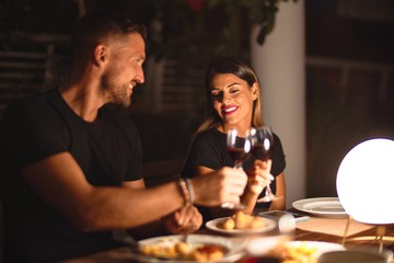 Obraz Young beautiful couple dinning on celebration toasting and smiling at terrace - fototapety do salonu