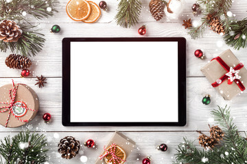Fototapete - Creative layout frame made of Christmas tree branches, pine cones and  tablet pc on white wooden  background. Xmas and New Year theme. Flat lay, top view, space for text