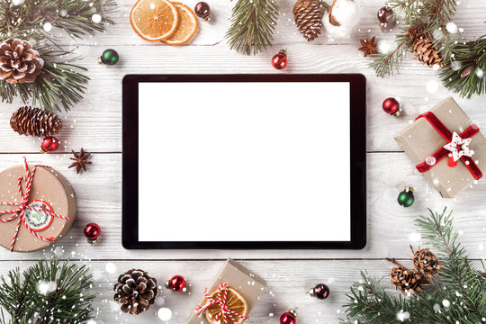 Creative layout frame made of Christmas tree branches, pine cones and  tablet pc on white wooden  background. Xmas and New Year theme. Flat lay, top view, space for text