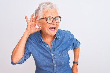 Fototapeta Senior grey-haired woman wearing denim shirt and glasses over isolated white background smiling with hand over ear listening an hearing to rumor or gossip. Deafness concept.