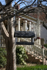 handmade bird feeder hanging in tree in front of old southern house