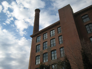 old historic mill building with smoke stack and large windows loft spaces