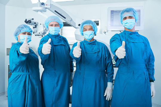 Team of surgeons in scrubs and face masks showing thumbs-up after suvcccessful surgery
