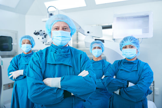 Confident team of surgeons in scrubs, caps and face masks standing with their arms folded and looking at camera