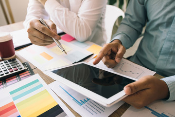 Two businessmen are working analyzing the company annual budget and using digital tablet to find information data result.
