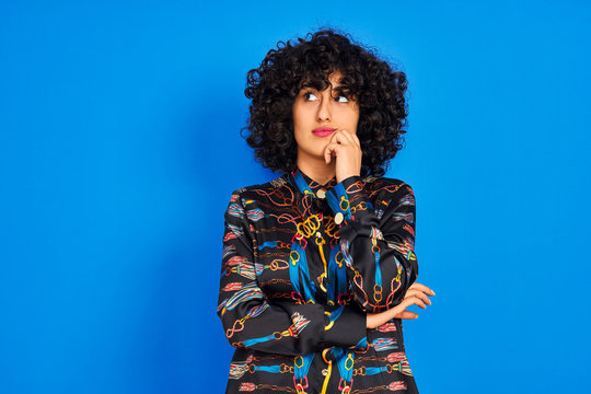 Young arab woman with curly hair wearing colorful shirt over isolated blue background with hand on chin thinking about question, pensive expression. Smiling with thoughtful face. Doubt concept.