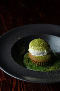 Close up of matcha cupcake with a scoop of vanilla ice cream on wooden table
