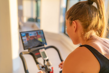 Fitness workout woman training at home on smart stationary bike equipment connected online live streaming class indoors for biking exercise. Indoor cycling. Focus on the sweat on person's back.