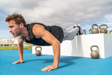 Decline push Up fitness man doing strength training exercise pushup at outdoor gym with feet elevated.