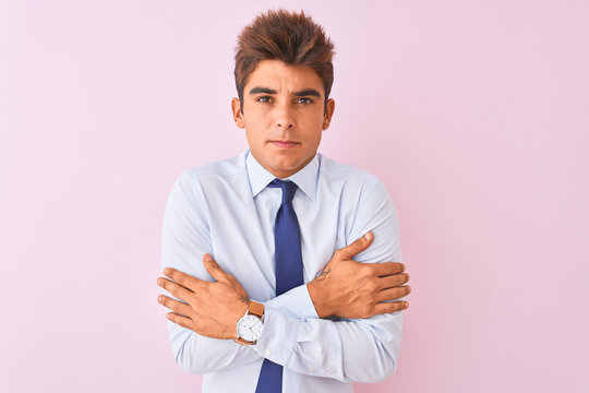 Young handsome businessman wearing shirt and tie standing over isolated pink background shaking and freezing for winter cold with sad and shock expression on face
