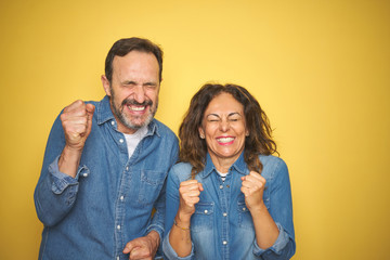 Beautiful middle age couple together standing over isolated yellow background excited for success with arms raised and eyes closed celebrating victory smiling. Winner concept.