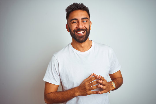 Young indian man wearing t-shirt standing over isolated white background Hands together and fingers crossed smiling relaxed and cheerful. Success and optimistic