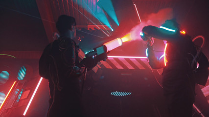 Two men in protective suits in a room with bright lasers