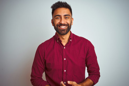 Young indian man wearing red elegant shirt standing over isolated grey background with hands together and crossed fingers smiling relaxed and cheerful. Success and optimistic
