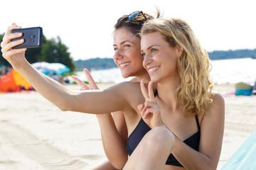 two female friends taking selfie on beach sending kisses