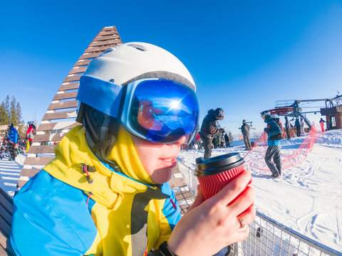 woman in ski mask and helmet drinking warm up tea on the top of the hill