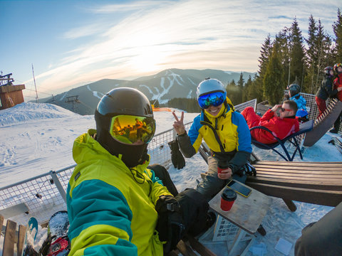 couple resting on the top of the hill drinking warm up tea and taking selfie. snowboarding skiing
