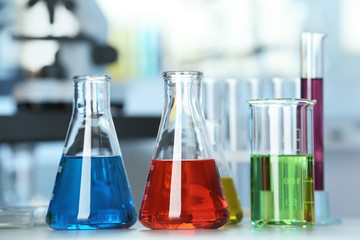 Fototapete - Glassware with colorful liquids on table in laboratory