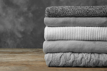 Fototapete - Stack of warm clothes on wooden table against grey background. Autumn season