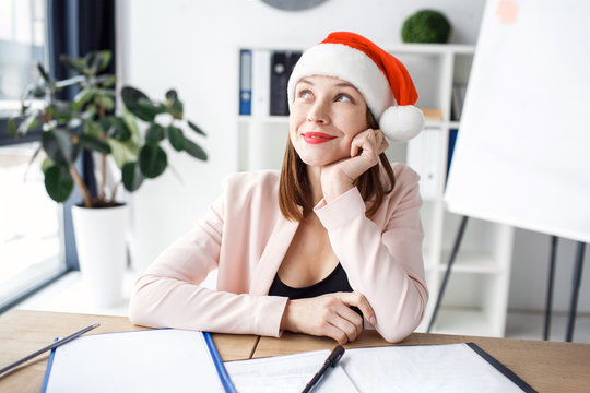 Dreamy positive and happy young woman look left up and smile. Wear red cap or hat. Festive mood. Celebrating new year or Christmas. Alone at work. Sit in office.
