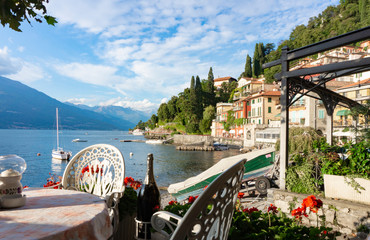 Scenic view of the Italian resort town of Varenna on the shores of the mountain lake Garda in the Alps. A cozy restaurant, old historic buildings, boats and yachts in the picturesque landscape