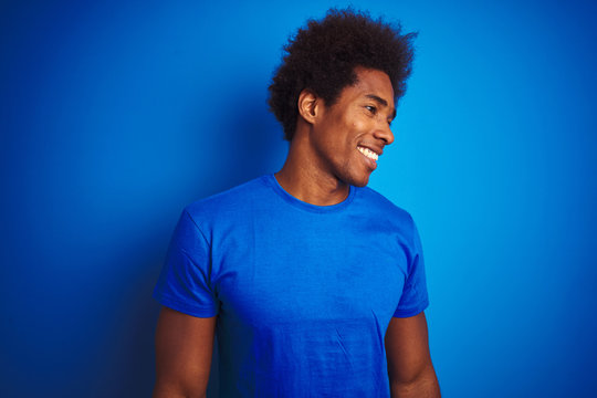 African american man with afro hair wearing t-shirt standing over isolated blue background looking away to side with smile on face, natural expression. Laughing confident.