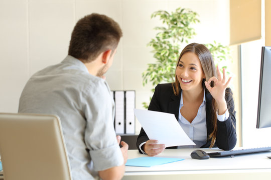 Manager interviewing a man holding resume gesturing ok