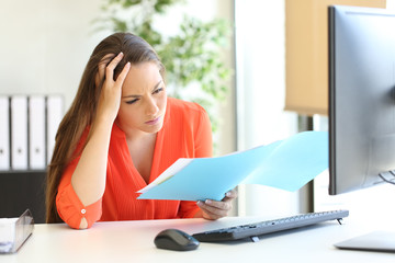 Worried busnesswoman discovering mistake on document