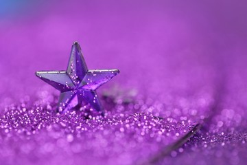 Christmas background.Violet star close-up on a lilac glitter background on a blurry purple...