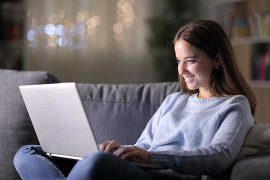 Happy woman using laptop on a couch at home in the night
