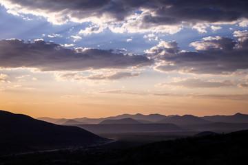 Papiers peints Aubergine Panorama au couché du soleil de montagnes et ciel orange avec nuages gris