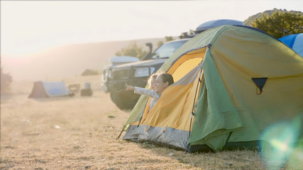 Tuinposter Kamperen Young mother with cute little daughter wakes up and looks out from tourist tent at campsite together. Expedition camp with off-road vehicle on the background, at morning in windy weather.