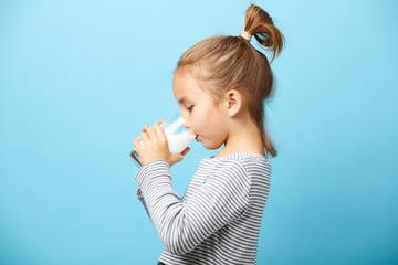 Fototapeta Child girl drinks milk without lactose, sideways portrait against blue isolated. obraz