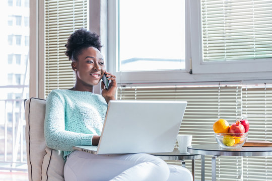 Portrait of a smiling young woman talking on mobile phone and working on laptop at home. Attractive young African woman working on laptop and smiling while sitting on the couch at home.