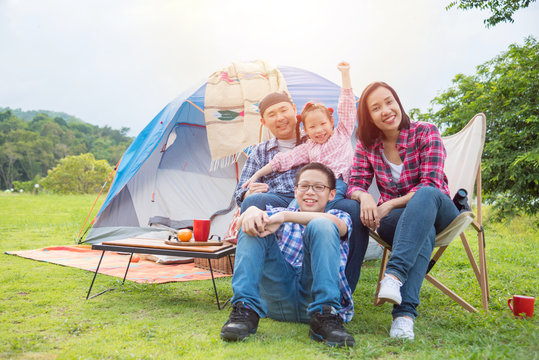 Group of asian family travel and camping in forest ,sitting all  together and smile. Family and outdoor activity concept.