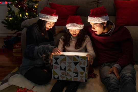 Happy family portrait, father mother and daughter, celebrate Christmas and New Year together, opening gift box with magically surprise