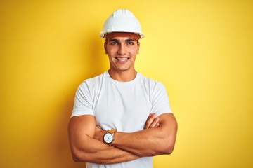 Young handsome man wearing construction helmet over yellow isolated background happy face smiling with crossed arms looking at the camera. Positive person.