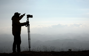 Silhouette image of photographer hold camera with tripod and point to the mountain over the cliff with morning light.