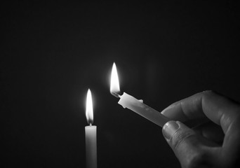 Black and white image concept, Candle light in a dark room., One candle flame at night