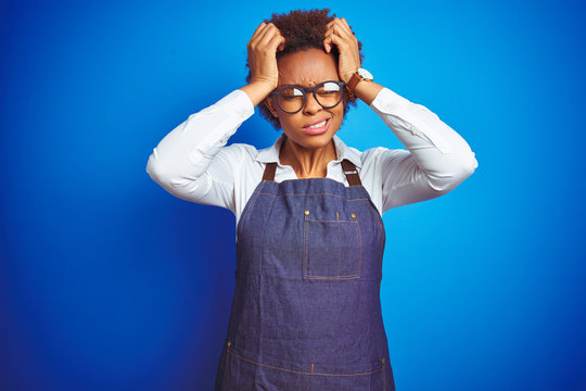 Young african american woman shop owner wearing business apron over blue background suffering from headache desperate and stressed because pain and migraine. Hands on head.
