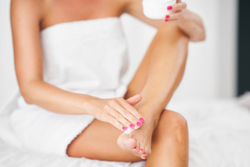 Adult woman applying body moisturizer
