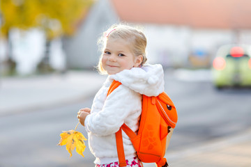 Cute little adorable toddler girl on her first day going to playschool. Healthy happy baby walking...