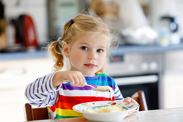 Adorable toddler girl eating healthy chicken noodle soup for lunch. Cute happy baby child taking food at home or nursery daycare or kindergarten and learning using spoon.
