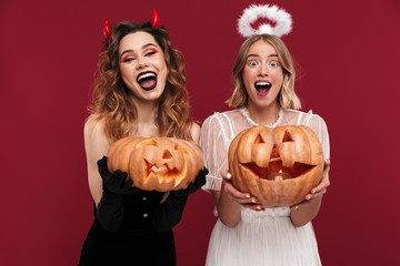 Positive women demon and angel in carnival costumes with pumpkin. Wall mural