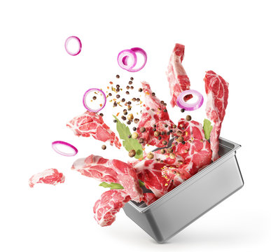 Cooking concept. Pieces of raw meat fly out of the capacity isolated on a white background. Splash.