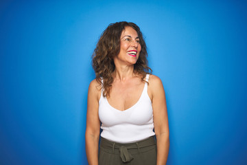 Wall Mural - Middle age senior woman with curly hair standing over blue isolated background looking away to side with smile on face, natural expression. Laughing confident.